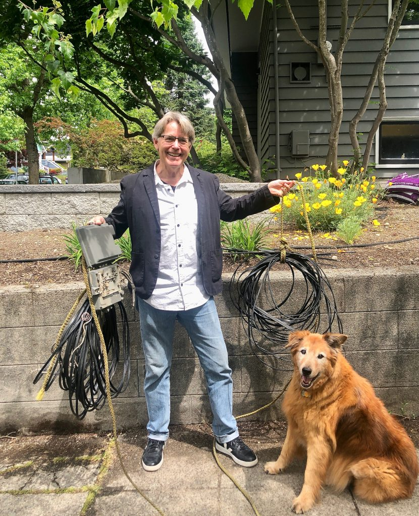 Photo of Rick & dog holding up the wires we took off his house