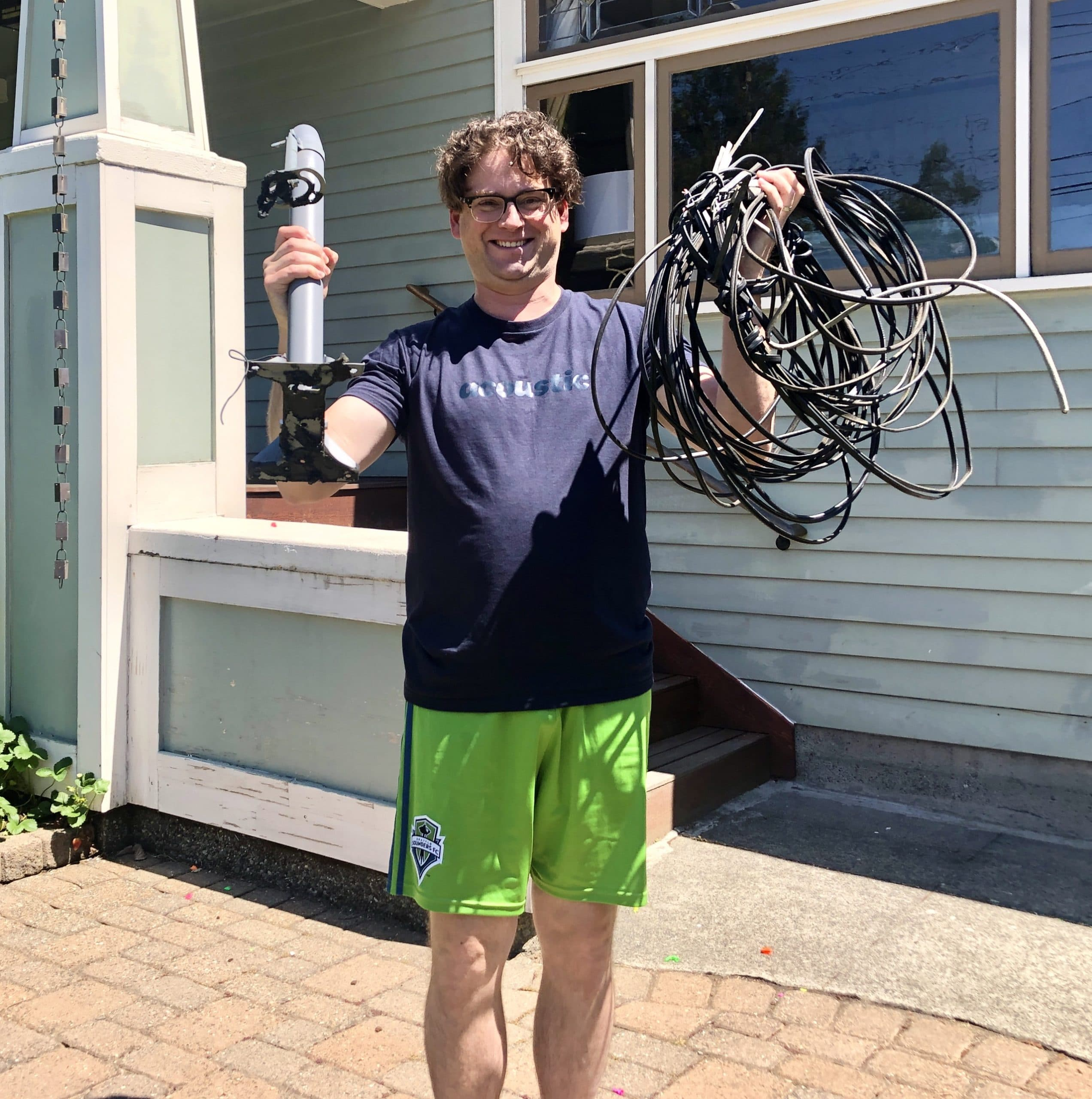 A happy man holding up wires we removed from his home