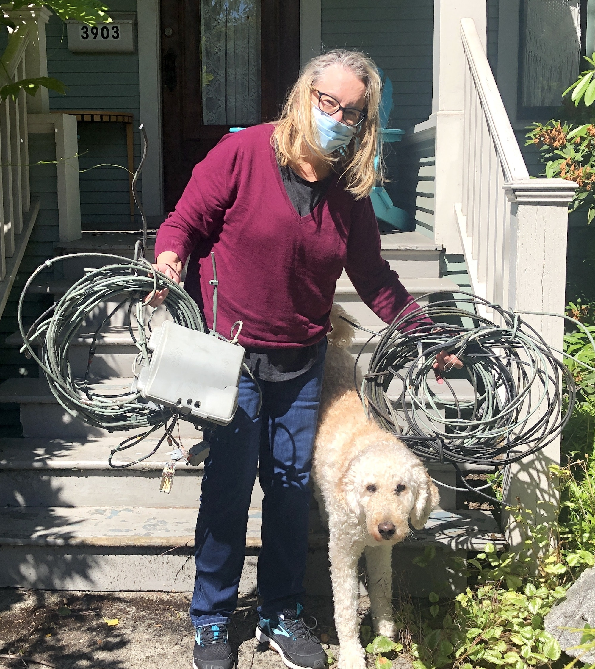 woman (and her dog) holding coil of wires we removed from her home