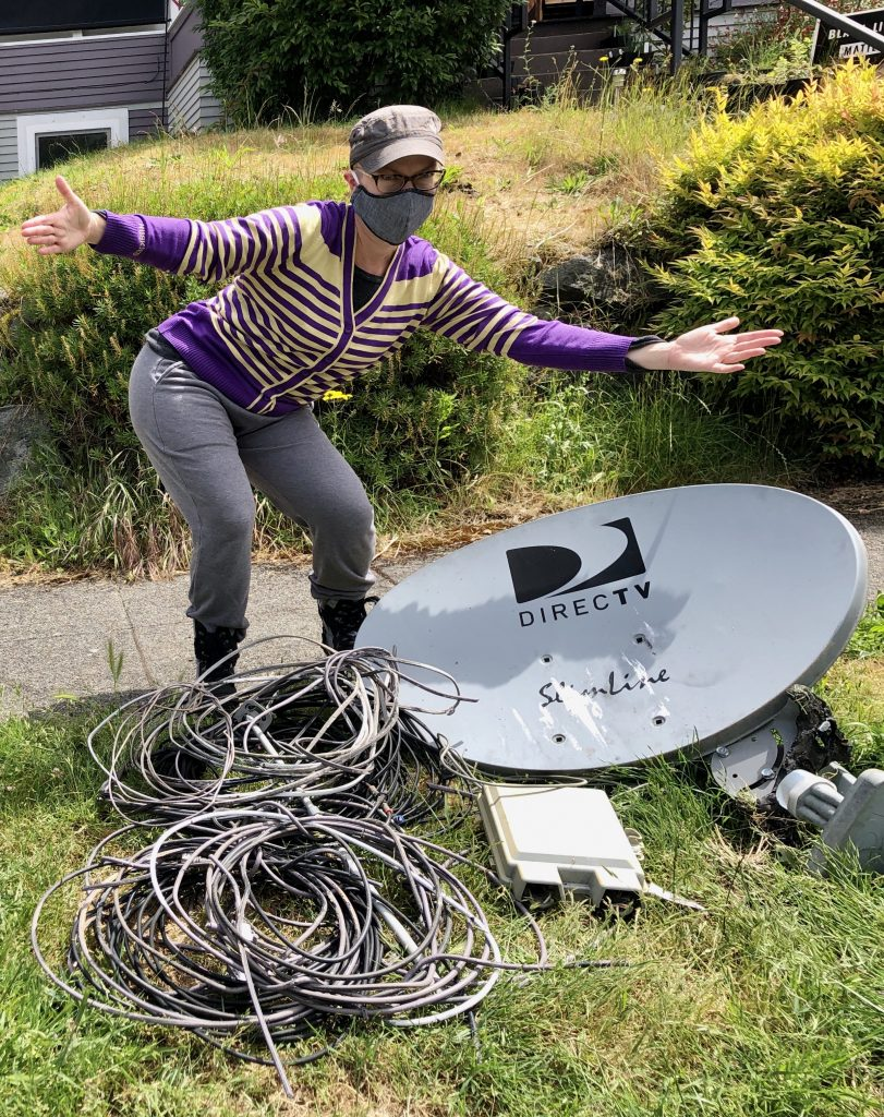 A woman showing off the wires and Satellite dish we removed from her home