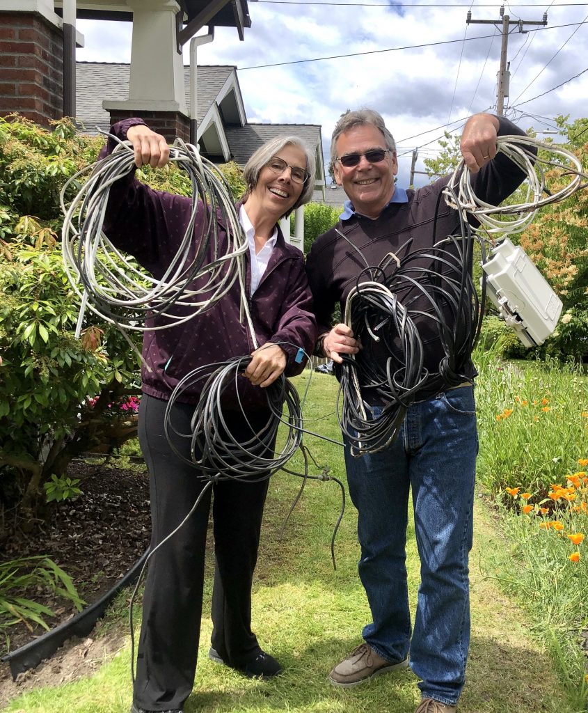 A couple holding up wires we removed from their home