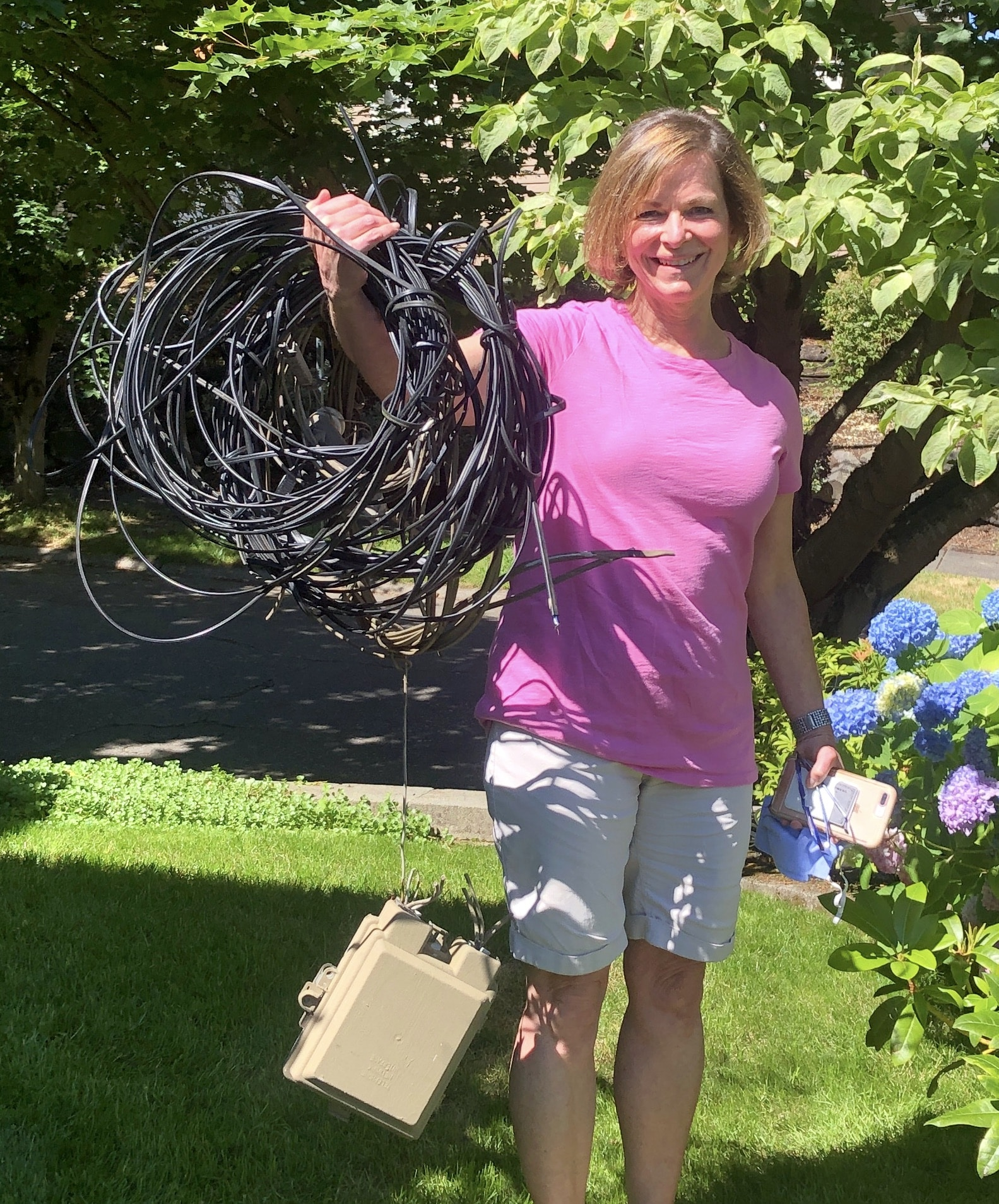 woman holding coil of wires we removed from her home