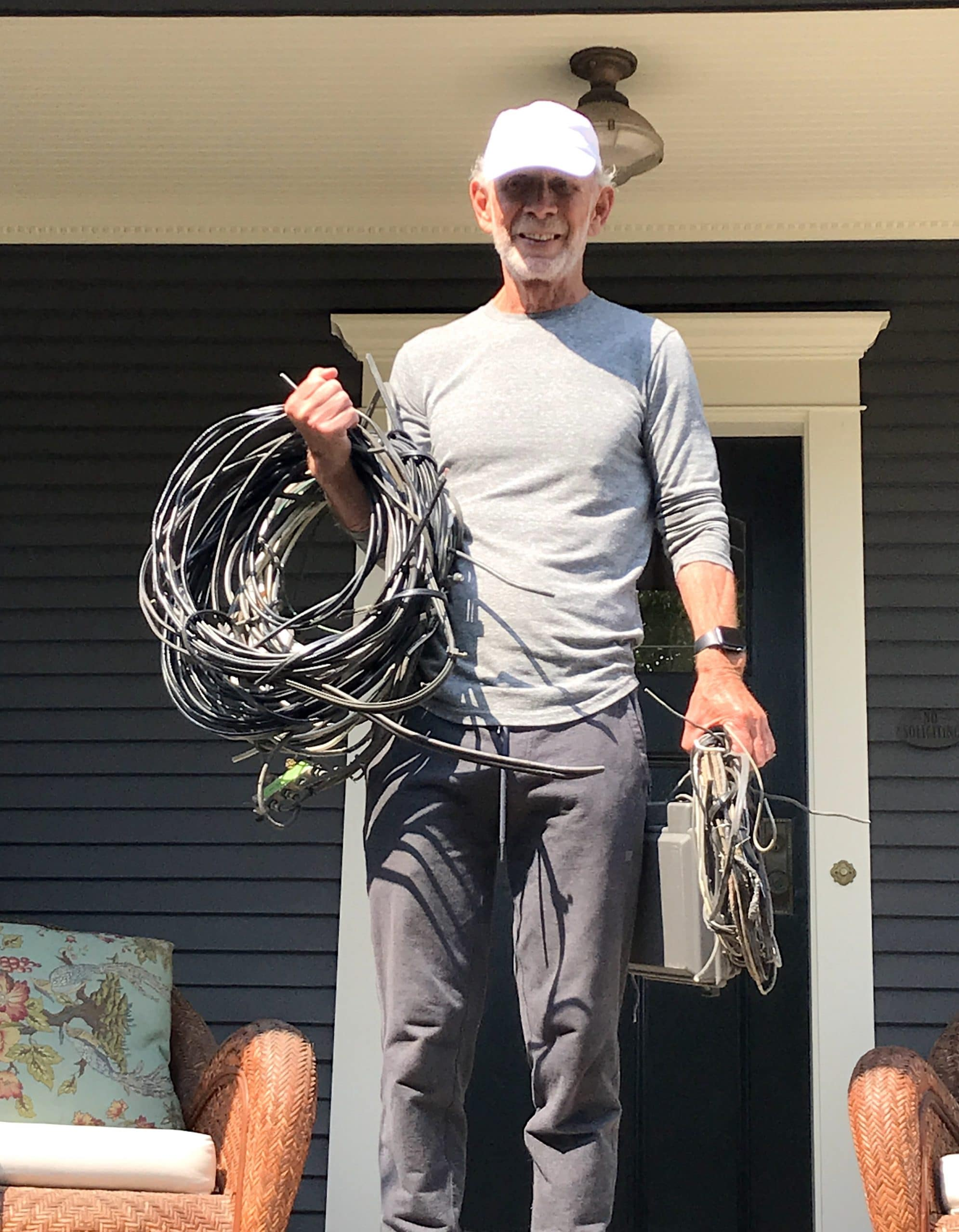 closeup of Man holding coil of wires we removed from his home