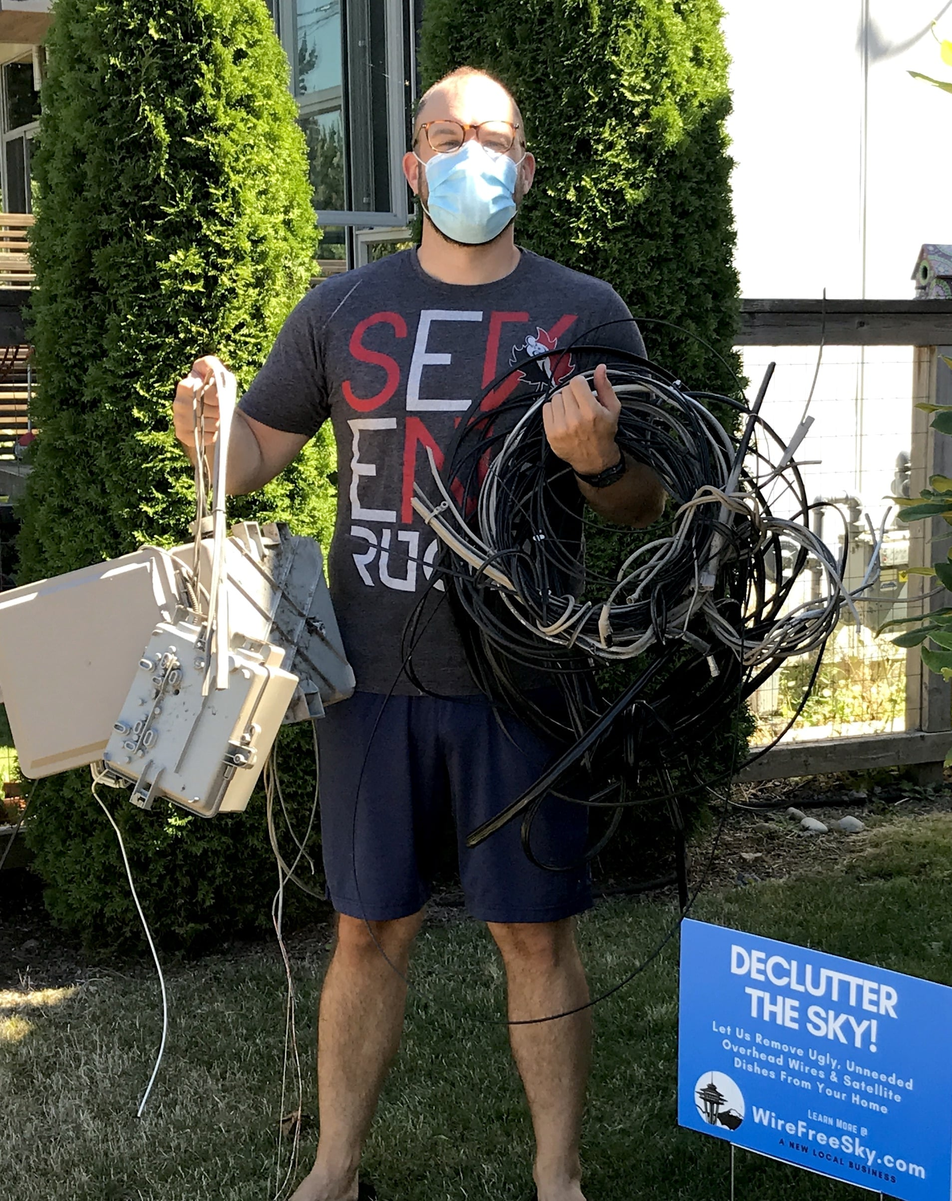 Photo of a man holding up the many overhead wires and service box just removed from house