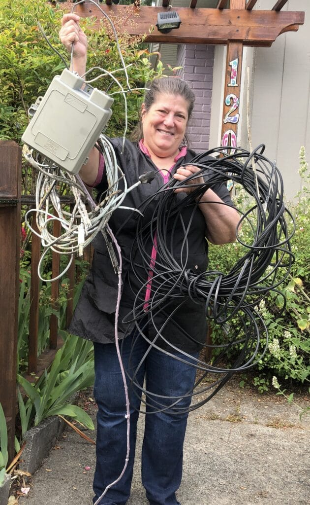 Photo of woman holding up overhead wires and service boxes just removed from home