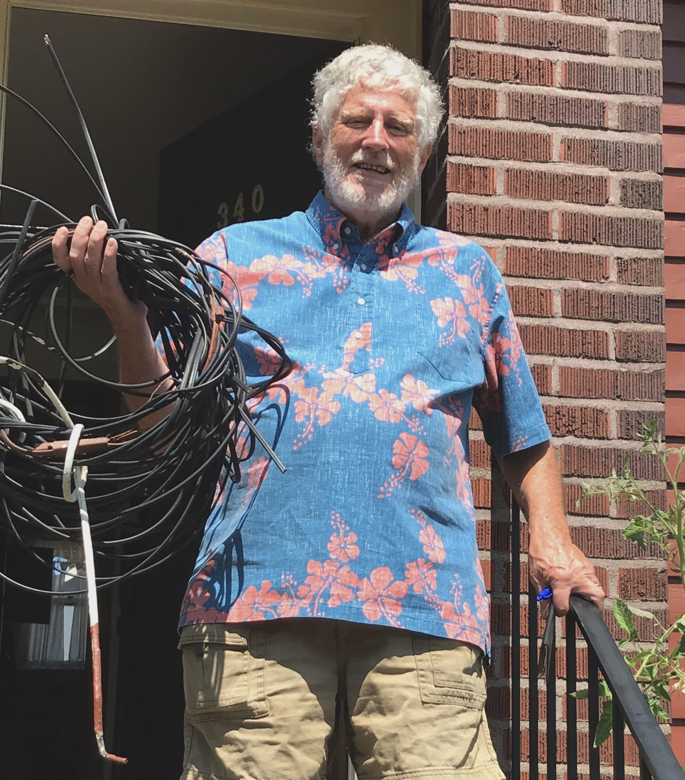 Photo of a man holding up the many wires removed from house
