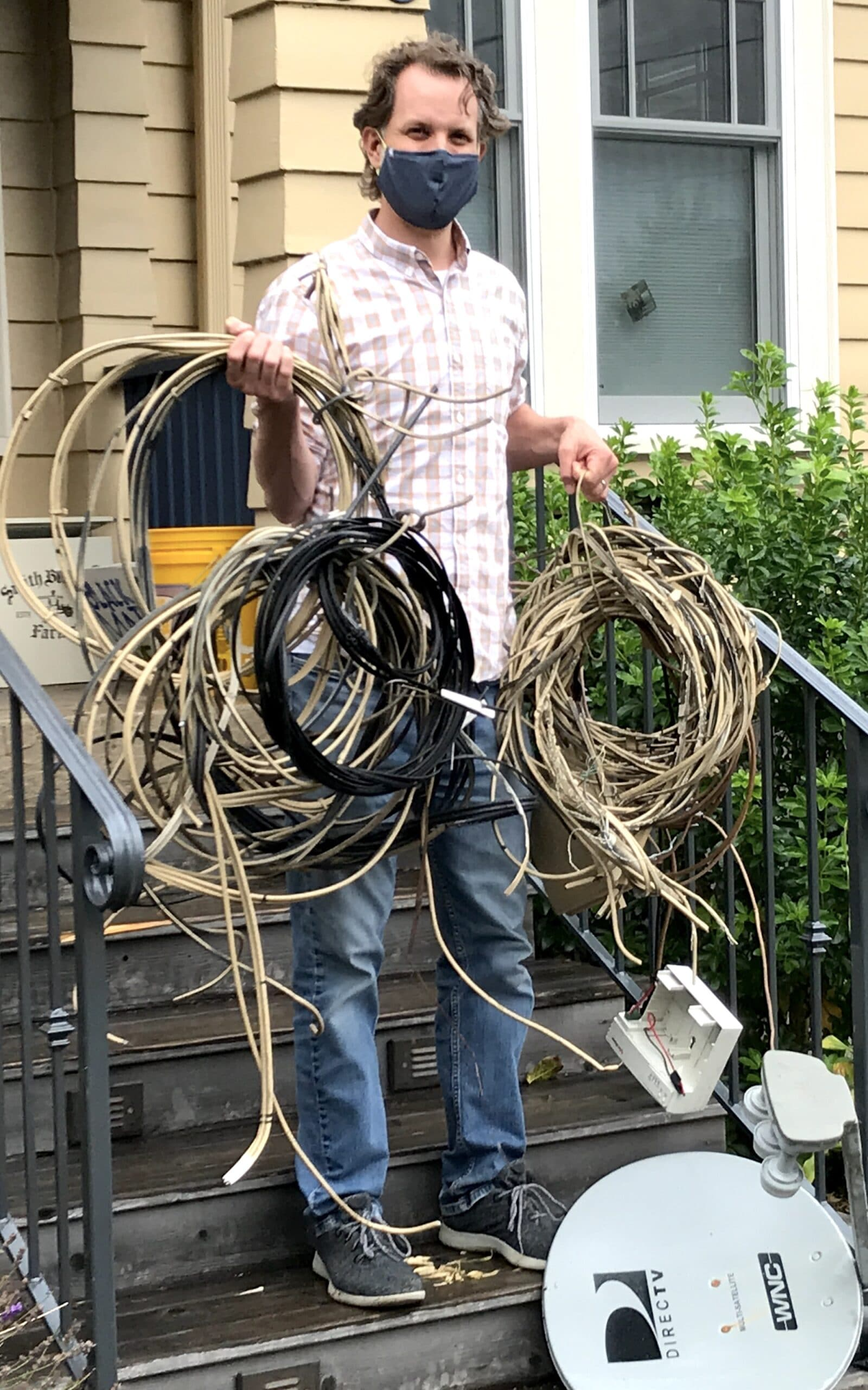 Photo of a man with the many wires and satellite dish just removed from house