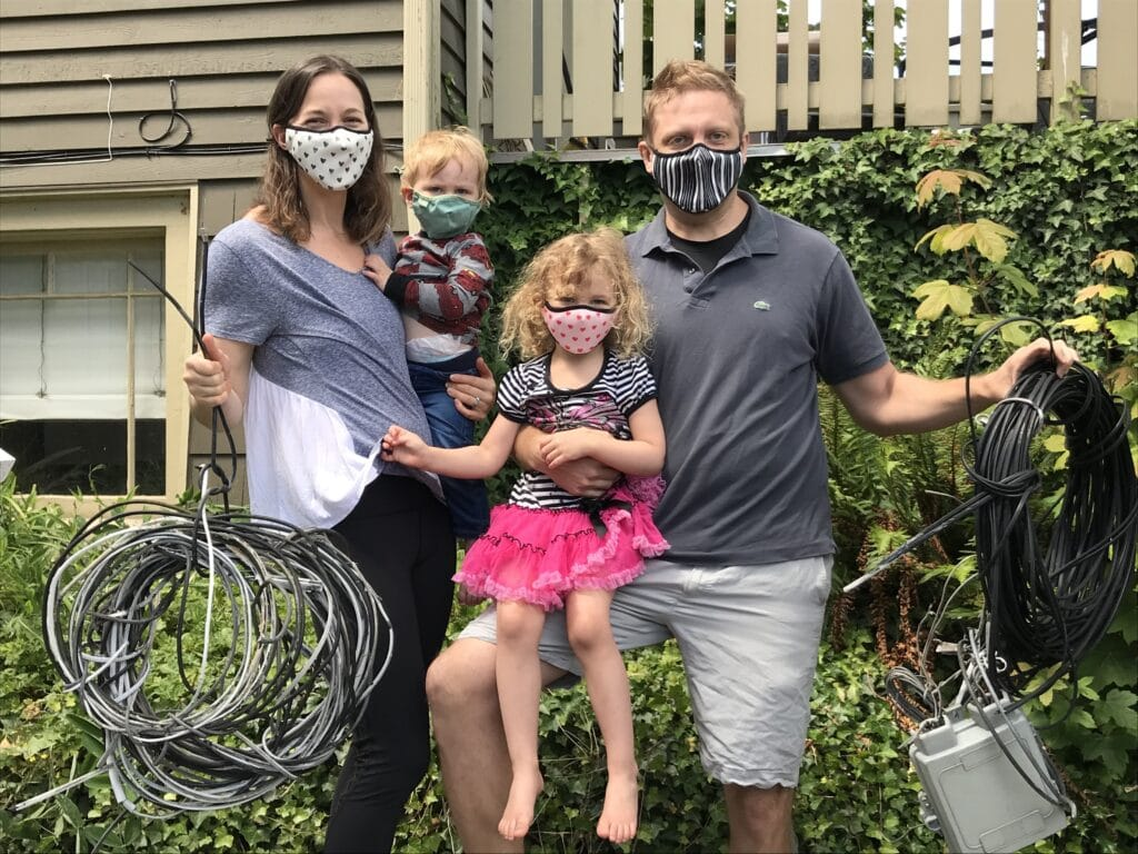 Photo of a young family holding the many wires removed from house