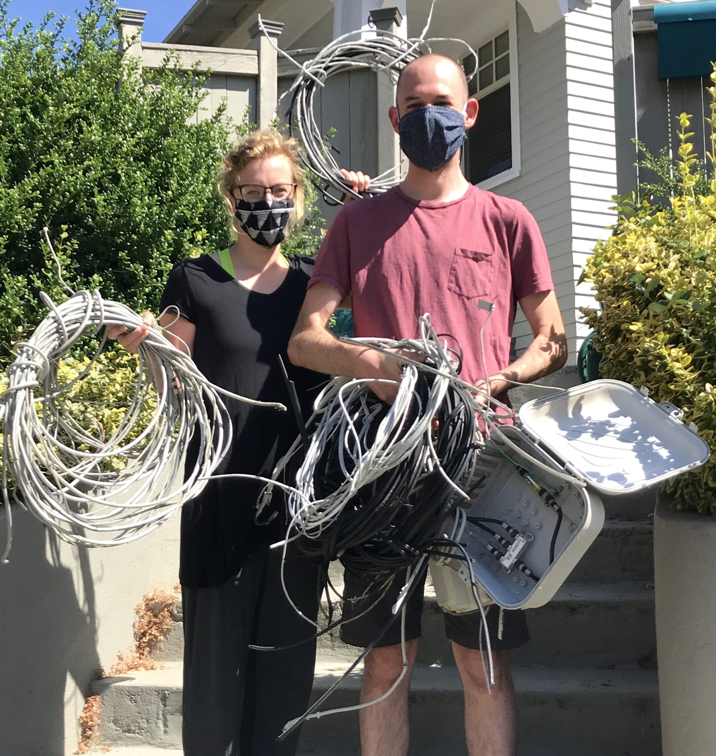 Photo of a couple holding the many wires just removed from house