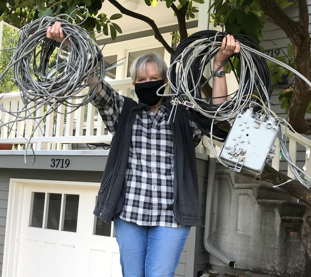 Photo of woman holding up wires and service boxes removed from home